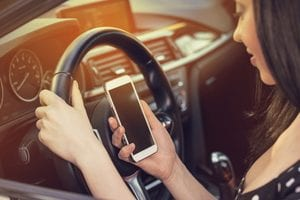 Girl looking at phone behind the wheel.
