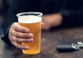 hand holding beer with keys
